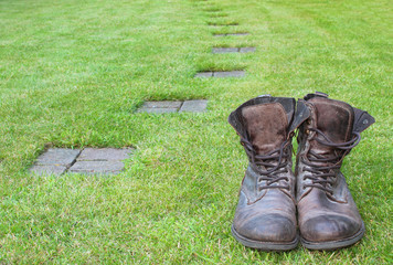 Worn boots next to a path