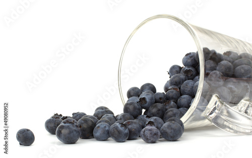 Blueberries closeup on white background rolling from cup