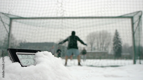 determined soccer players in winter time thermometer in foregrou