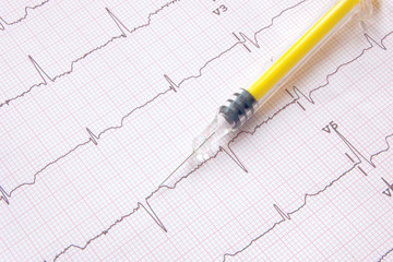 electrocardiogram with yellow colored syringe