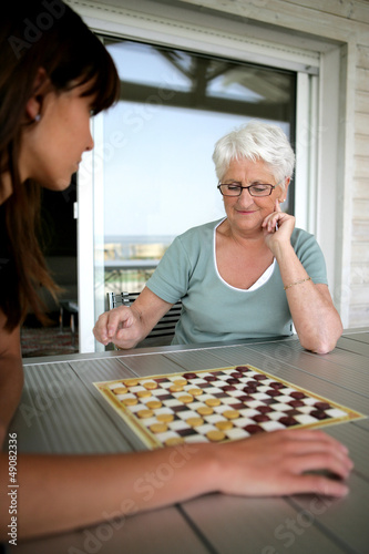 Young woman and senior woman playing checkers