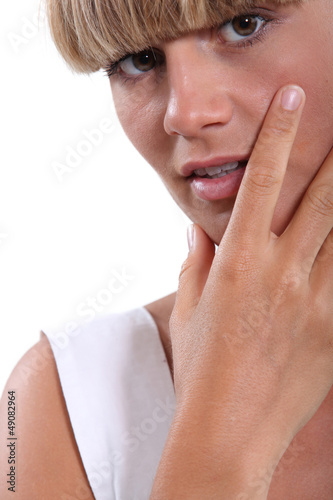 Young woman with her hand to her face