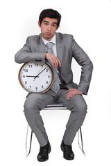 Businessman bored with alarm clock