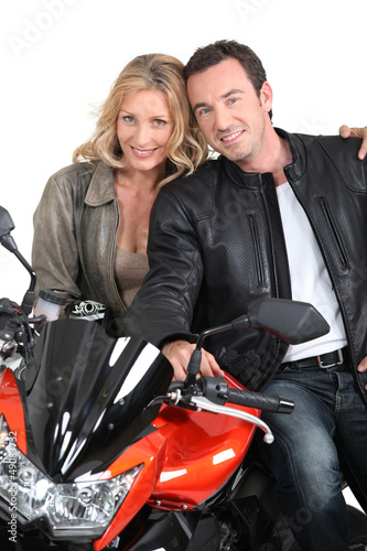 Biker chic with arms around biker.