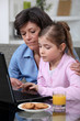 Child and her grandmother using a laptop
