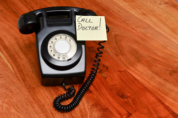 Black retro telephone with reminder note to call the doctor