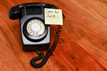 Black retro telephone with reminder note to call in sick at work