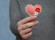 red heart in woman's hand on blue background, close-up