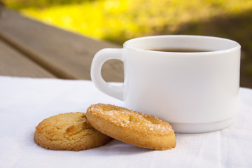 White cup of coffee with cookies on wooden table.