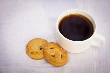 White cup of coffee with cookies on cloth.