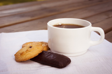 Cup of coffee with cookies and chocolate on wooden table.