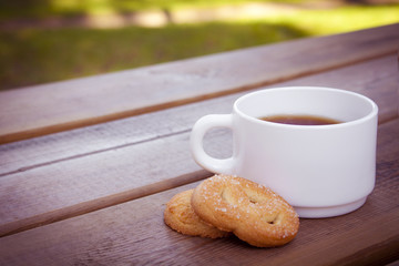 Cup of coffee with cookies on wooden table.