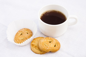 Cup of coffee with cookies on white cloth.
