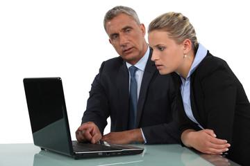 businessman and businesswoman analysing data on their laptop