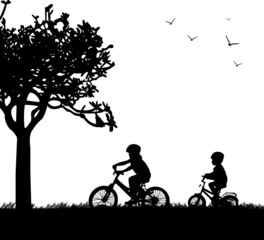 Kids bike ride in park in spring silhouette
