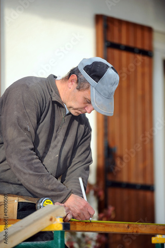 Man marking plank before cutting it