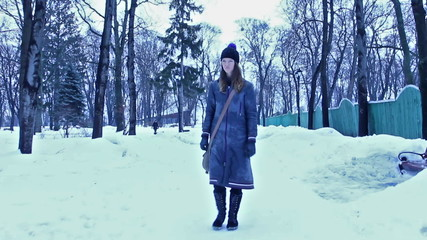 The winter girl in city park walking. Stabilized shot