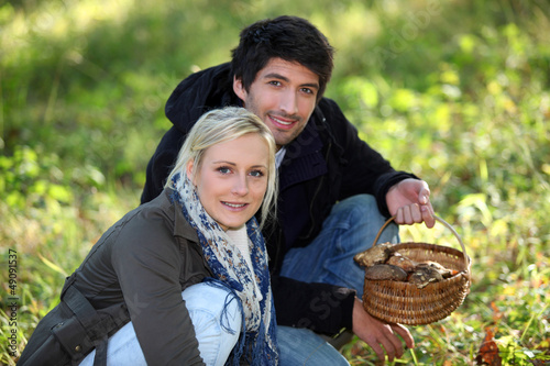 Couple with basket of mushrooms