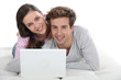 Young couple posing with their laptop