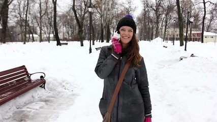 young nice girl speaks by  mobile phone in winter park
