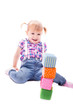 Kleines Mädchen baut mit Würfeln einen Turm