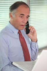 mature businessman on the phone looks stunned