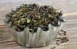Loose green tea leaves in a metal cupcake