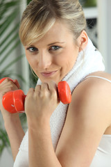 Blond lifting weights in gym