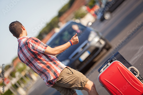 Young Man Hitchhiking along the Road
