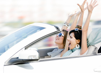 Female friends driving cabriolet with the hands up