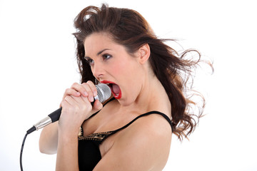 Woman singing loudly into a microphone