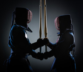 Two kendoka opposite each other with wooden sword