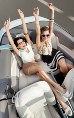 Top view of happy women in sunglasses with sit in the cabriolet