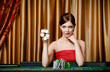 Female gambler shows chips in hand sitting at the playing table