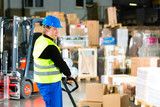 Fototapety Storeman with mover at warehouse of forwarding