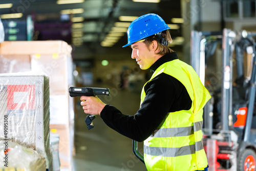 Warehouseman in protective vest using a scanner