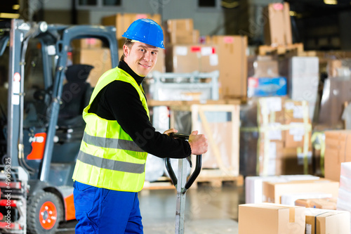 Storeman with mover at warehouse of forwarding - 49095325