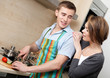Man in apron chops vegetables for dinner for his girlfriend