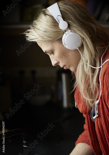 Blonde young woman listens music by headphones