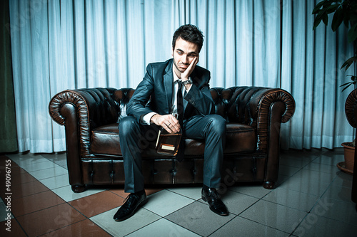 Drunk businessman with a bottle of strong alcohol
