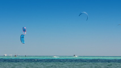 kite surfing - surfers on blue sea surface