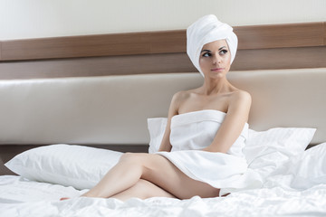 Sexy woman sitting on bed after bath in hotel room