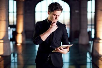 Homme se questionnant face à une tablette