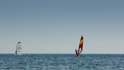 windsurfing - surfers on blue sea surface
