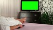 Woman watches television with green screen