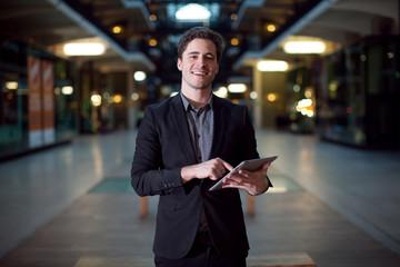 Homme caucasien souriant avec une tablette