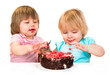 Two little baby girl eating cake