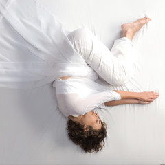 Woman in fetal position on white background