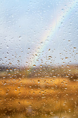 Rainbow through rained window with droplets