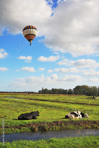 In cloudy sky flying multicolored balloon